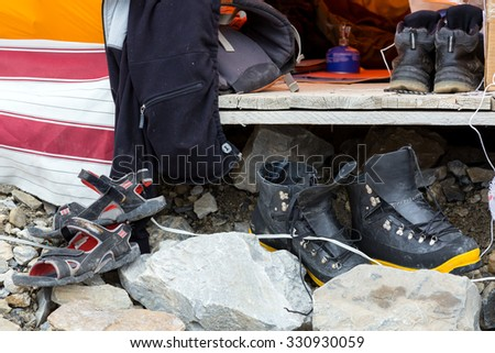 Variety of Footwear Used by Members of Alpine Climbing Mountain Expedition Composition with Variety of Boots Beach Sandals Heavy Mountain Plastic Boots Moderate Hiking Shoes All Dirty and Old - stock photo