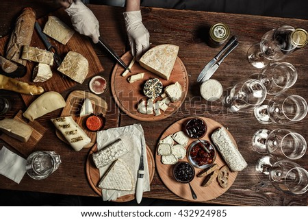 Variety of french cheeses with different spices on the wooden board background. Food concept - stock photo