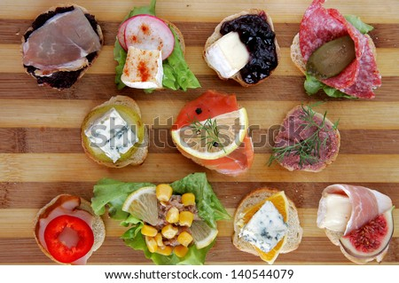 Variety of fresh canapes on a cutting board - stock photo