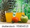 variety of fruit and juice on a wooden table in the garden - stock photo