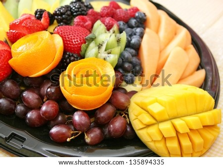 Variety of fruit on a plate includes strawberry, grapes, blueberries, blackberries, kiwi, melon, raspberry, mango,tropical, juicy, fresh, healthy - stock photo