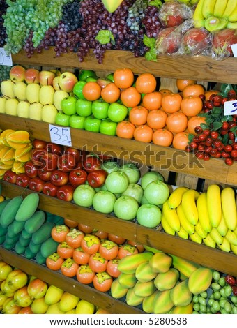 Variety of fruits and vegetables at fruit stand at Thai weekend market.
