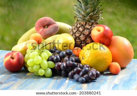 variety of fruits on table in the garden - stock photo