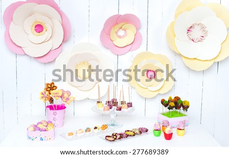 Variety of fruits (strawberry, banana, grape, pineapple) covered with a color chocolate, decoration of birthday party table - stock photo