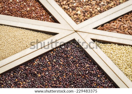 variety of gluten free grains (red and black quinoa, buckwheat, brown rive, amaranth and millet) in a wooden tray, focus on black quinoa - stock photo