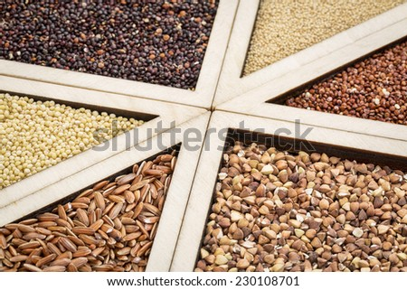 variety of gluten free grains (red and black quinoa, buckwheat, brown rive, amaranth and millet) in a wooden tray, focus on buckwheat and rice - stock photo
