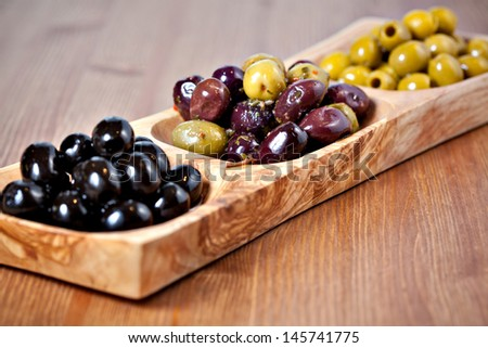 Variety of green, black and mixed marinated olives in olive tree dish on wooden table. Selective focus - stock photo