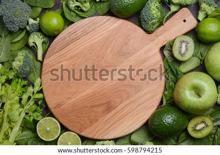 Variety Of Green Fruits And Vegetables With Empty Wooden Cutting Board. Top  View, Copy