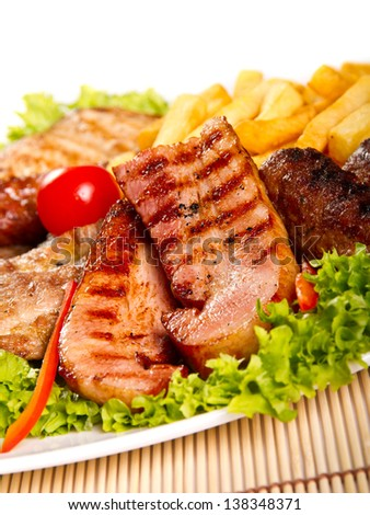 Variety of grilled meat  with fries