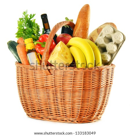 Variety of grocery products in wicker basket isolated on white - stock photo