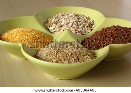 Variety of healthy grains and seeds in bowl: buckwheat, oatmeal, rice, corn - stock photo