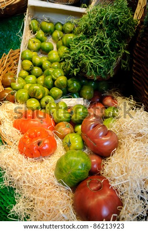 Variety of heirloom tomatoes at a farmers market in Paris. There are shades of red, green, yellow, and purple vegetables. Loose tomatoes in the foreground and a basket full in the back. - stock photo