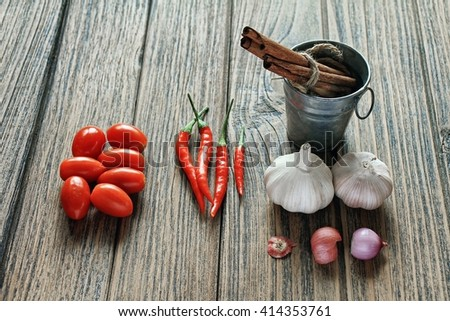 Variety of herb and spices on wooden background. Shallot, Cardamom, Cinnamon sticks, Fresh garlic, Red Chilli pepper. Healthy ingredients, Cuisine ingredients. - stock photo