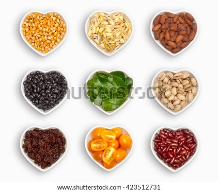 variety of ingredients in a heart shaped bowl, isolated on white corn, fresh soya, roasted almonds, black beans, bergamot, pistachio, raisins, plum tomato, red bean,