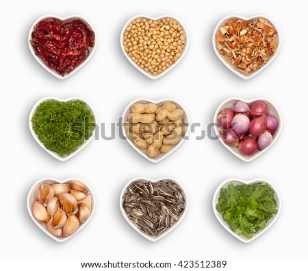variety of ingredients in a heart shaped bowl, isolated on white dried chili, coriander seeds, lemon grass, parsley, peanuts, shallot, garlic, sunflower seeds, fresh coriander