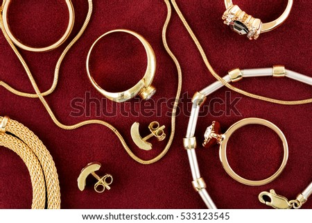 variety of jewelry items on red felt texture