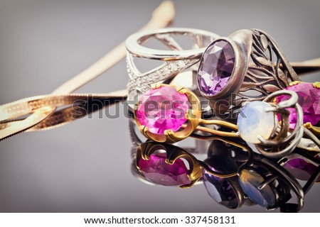 variety of jewelry made of precious metals: rings and earrings in gold and silver with inlays of different precious stones - stock photo