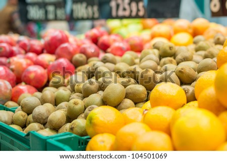 Variety of kiwi fruits and pomegranate fruits in boxes in supermarket