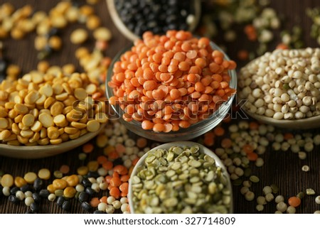 Variety of lentils kept on wooden background