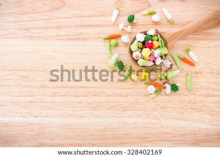 Variety of miniature clay vegetables on wooden spoon ; food and health concept background with copy space - stock photo
