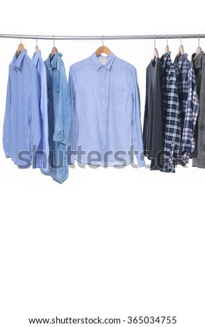 Variety of multicolored casual men's clothes shirts ,jacket on hangers - stock photo