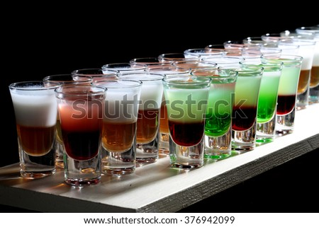 Variety of multicolored red freen white orange tasty tropical cocktail shots alcoholic liquid for party in beautiful glasses standing in line on bar on black background closeup, horizontal picture - stock photo