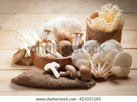 Variety of Mushrooms in a basket on wood