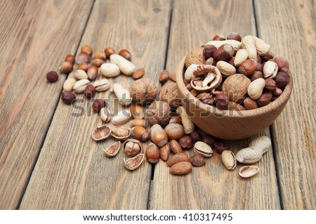 Variety of nuts: walnut, hazelnut, hazelnuts, peanuts, pine nuts and other on a wooden background - stock photo