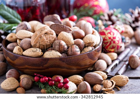 Variety of nuts with shells in a brown bowl