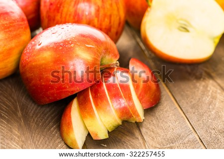 Variety of organic apples sliced on wood table. - stock photo