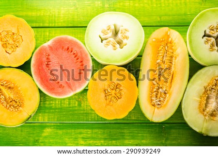 Variety of organic melons sliced on wood table. - stock photo