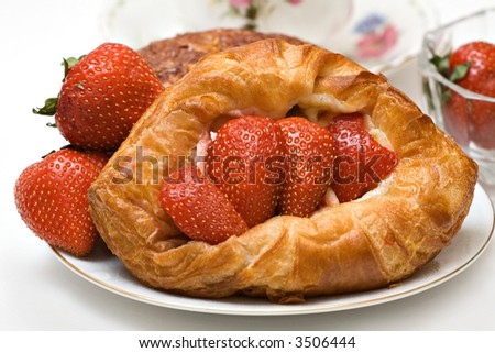 Variety of pastries featuring a strawberry danish - fresh strawberries, cup saucer visible