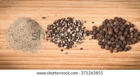 Variety of pepper including ground, crushed and whole peppercorns on wooden background - stock photo