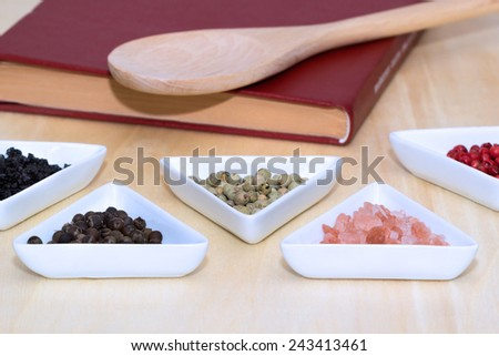 Variety of peppercorns and salt with closed cook book and spoon