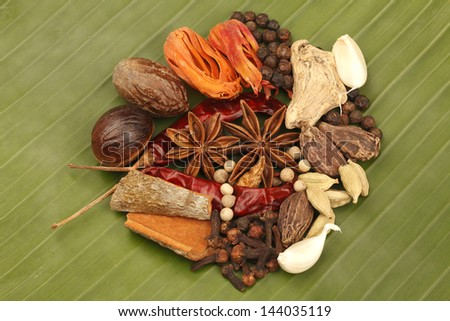 Variety of raw Authentic Indian Spices on green Banana leaf. - stock photo