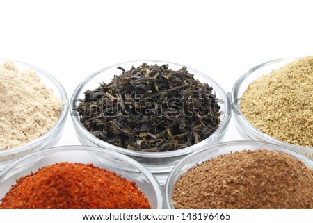 Variety of raw Authentic Indian Spices Powder on glass bowl isolated on white background in full-frame. - stock photo