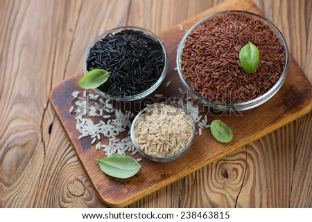 Variety of raw rice, rustic wooden background, high angle view - stock photo