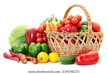 Variety of raw vegetables in wicker basket isolated on white.