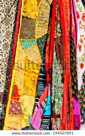 Variety of samples of bright, colorful silk fabric in oriental style for a decoration, needlework and  clothes purposes. A street bazaar at a flea market in Tel Aviv. Israel - stock photo