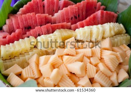 Variety of sliced fruits on banana leaf - stock photo