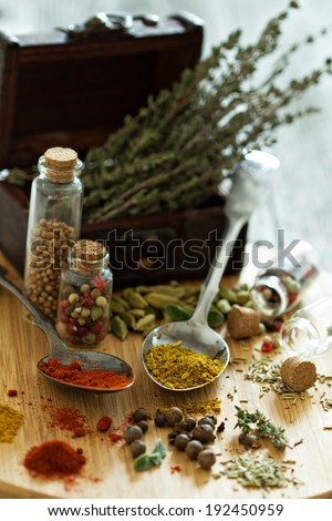 Variety of spices and herb on a wooden board - selective focus