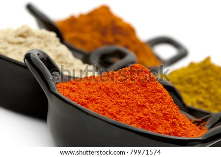 Variety of spices in small black bowls.  Focus on front bowl.  Includes saffron, ginger, and curry powders. - stock photo
