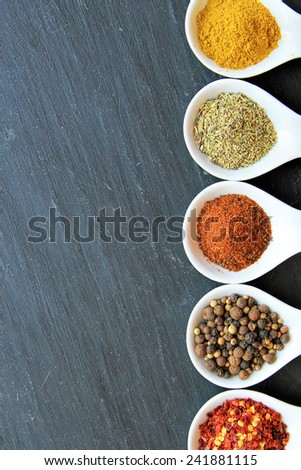 variety of spices on a black slice. From  up to down: curry powder, Provencal Herbs, paprika,  Black Peppercorn, espelette chili,  - stock photo