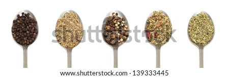 variety of spices on metal spoon over white background - stock photo