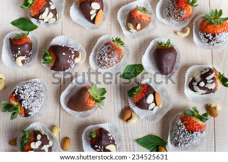 Variety of strawberries covered with a milk, dark and white chocolate and nuts, on the light wooden table - stock photo