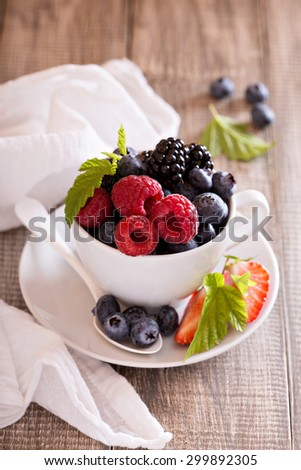 Variety of summer berries in a white cup
