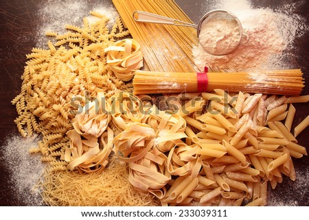 Variety of types and shapes of pasta with white flour - stock photo