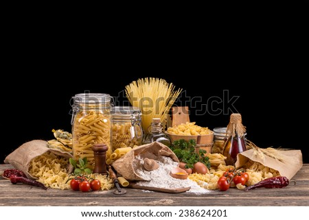 Variety of uncooked pasta on wooden board - stock photo