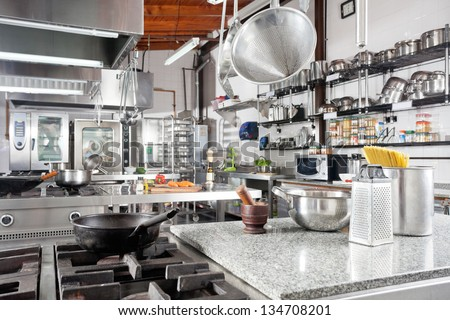Variety of utensils on counter in commercial kitchen - stock photo