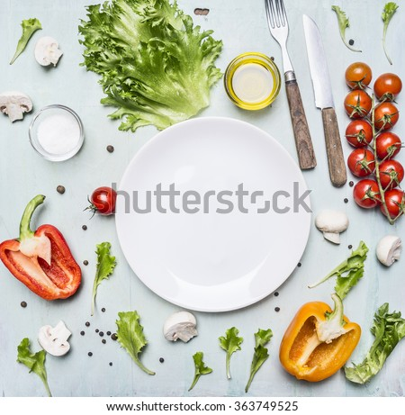 variety of vegetables laid out around a white plate with oilknife and fork on wooden rustic background top view close up - stock photo